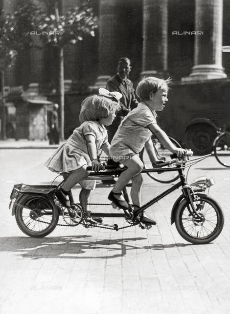 Two children on a tandem bike in Paris