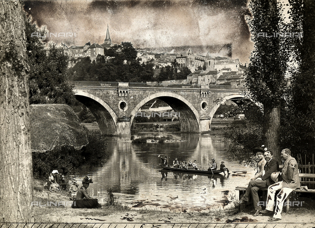 View of Liverdun and its bridge. In the foreground, some people resting on the riverbank.