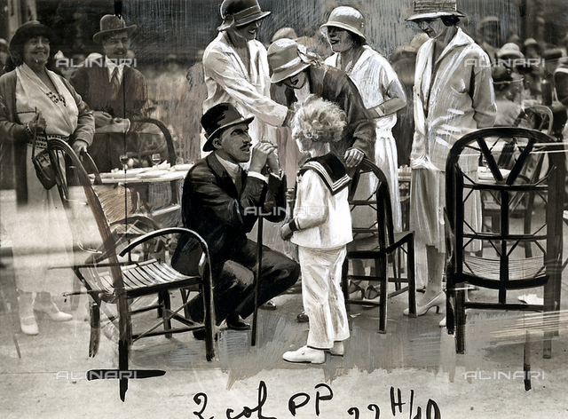 Snapshot of King Alfonso XIII of Spain, speaking with a child at Potiniére di Deuville.