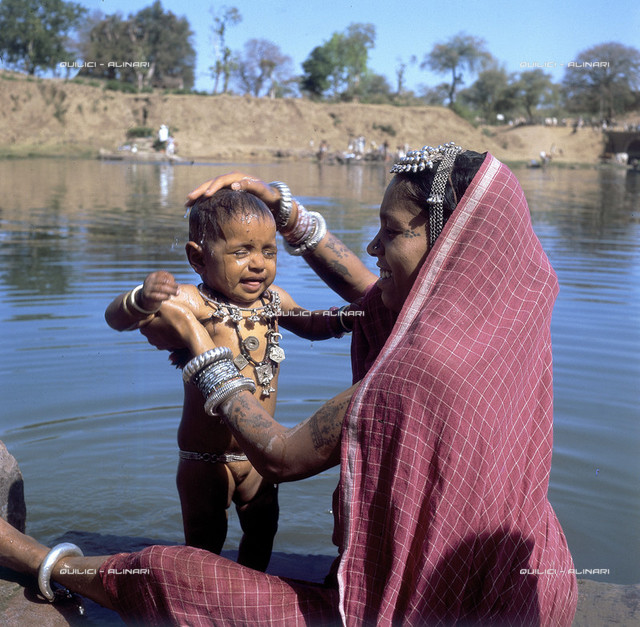 Portrait of an Indian woman with a child in the river, region of Malabar, state of Kerala, Southern India