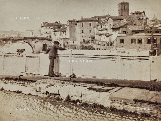 Guy on the parapet of the Ponte Emilio (today Ponte Rotto) in Rome. In the background the Tiber Island with the Ponte Cestio