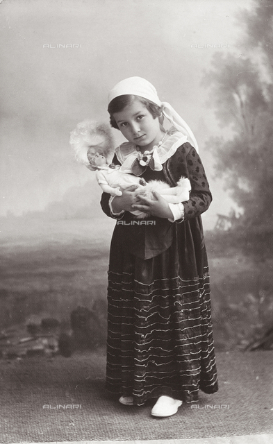 Portrait of little girl in costume with doll