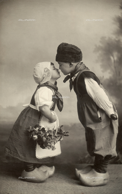 Two De Angelis children in Dutch costume photographed in the tender moment of kissing