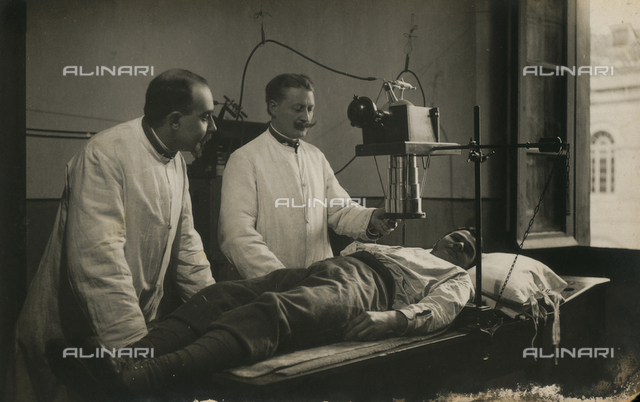 Two doctors conducting a radiological exam on a patient lying on a bed in the Military Hospital in Campobasso