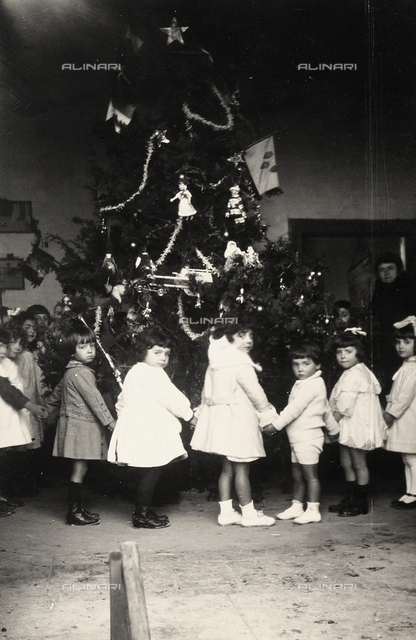 A group of children in maternal school photographed while making a circle around a Christmas tree