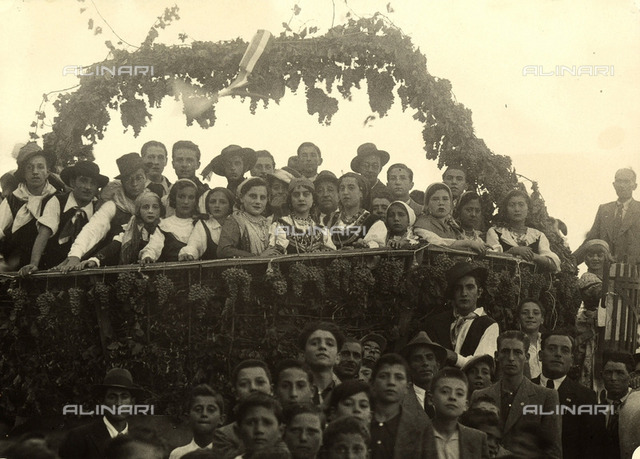 Group of men and women in traditional costume photographed on a carriage, decorated with bunches of grapes