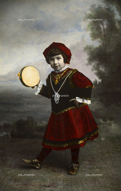 Portrait of a girl wearing traditional costumes with a tambourine