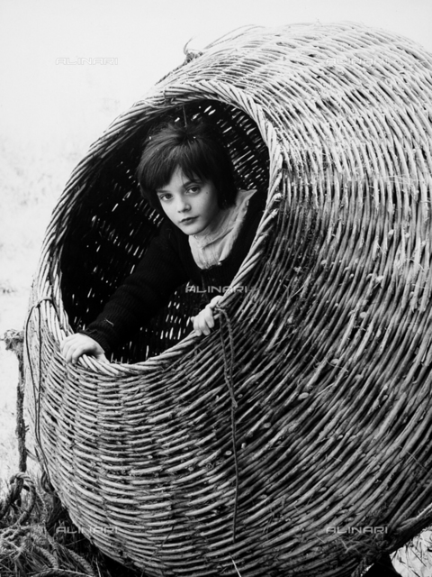 "The young actor Claudio De Cunere inside a basket. He plays the role of the young Giacomo Casanova during the shooting of the film ""Infanzia vocazione di Giacomo Casanova veneziano""."