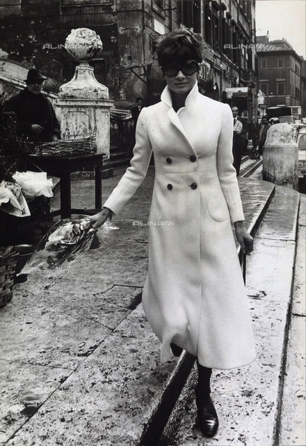 The actress Audrey Hepburn walking in the Piazza di Spagna with a bouquet of flowers in her hand.