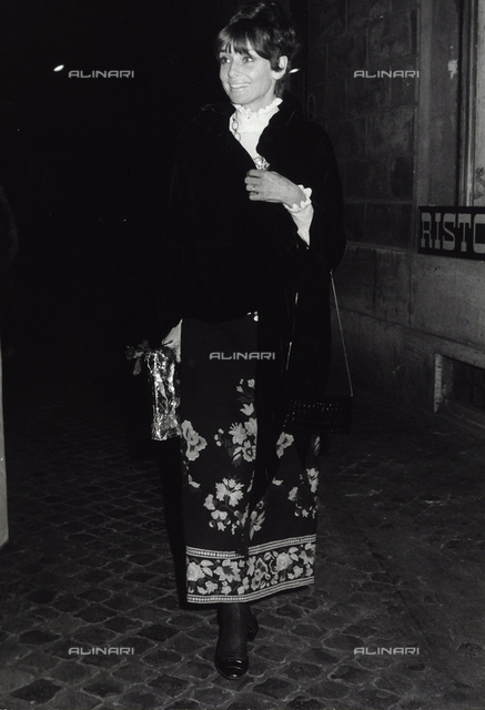 A smiling Audrey Hepburn walking on a street in Rome at night.