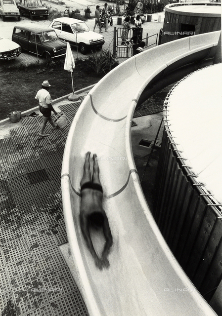 A man quickly sliding down a tube in a swimming pool. In the background a parking lot with cars and people at the entrance gate are visible