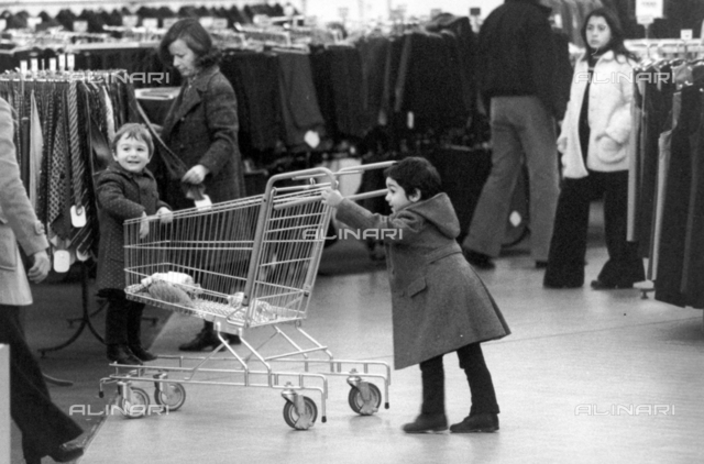 Children with a shopping cart inside a clothing store