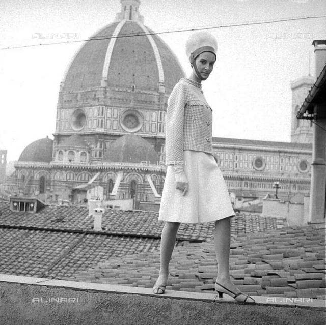 A creation of the fashion designer Emilio Pucci in Florence of the autumn-winter collection of 1965. The model is wearing a cream-colored wool skirt to the knee and a short jacket with reversible barrel neck cream and beige, a hat with a rounded chin. In the background the dome of Florence Cathedral