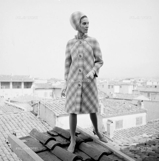 The designer Emilio Pucci creation of the 1965-1966 collection. Model wears a wool dress coat-colored geranium characterized by a drawing in a herringbone pattern and the front buttons. The hat, reminiscent of a helmet, is matched to the dress