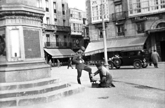 Spanish Civil War 1936-1939: Soldier standing while a shoe shine polishes his boots in the square of a town