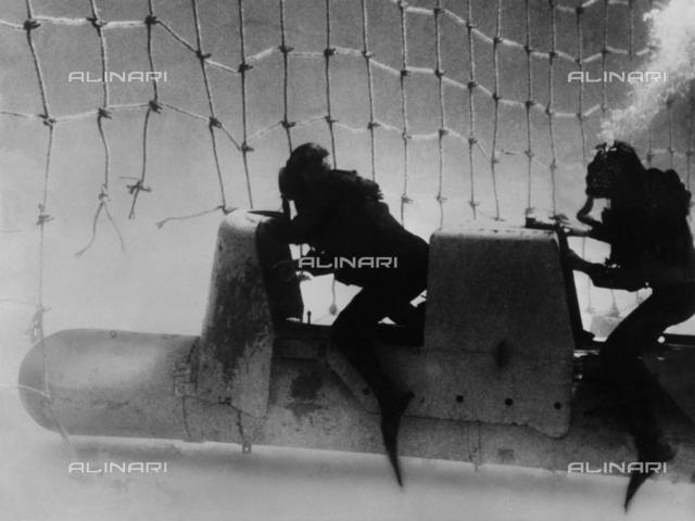 World War II: Italian frogmen, riding a submarine torpedo, break through the British network barrier in front of Gibraltar