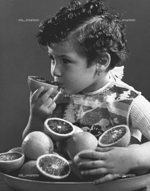 Photo of a little girl sucking an orange