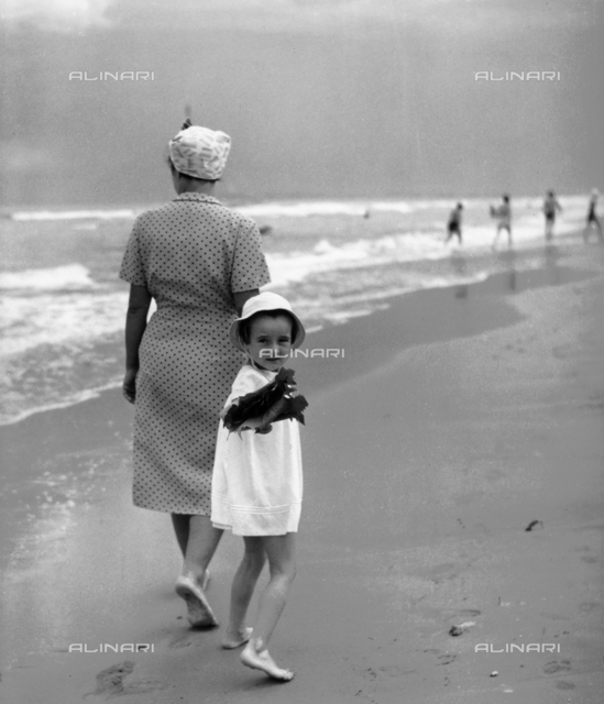 Little girl walking on the beach holding hands with mother