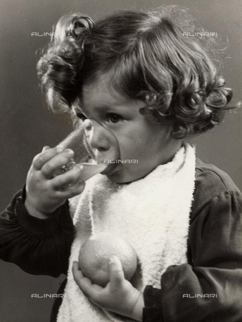 Photo of a little girl drinking orange juice