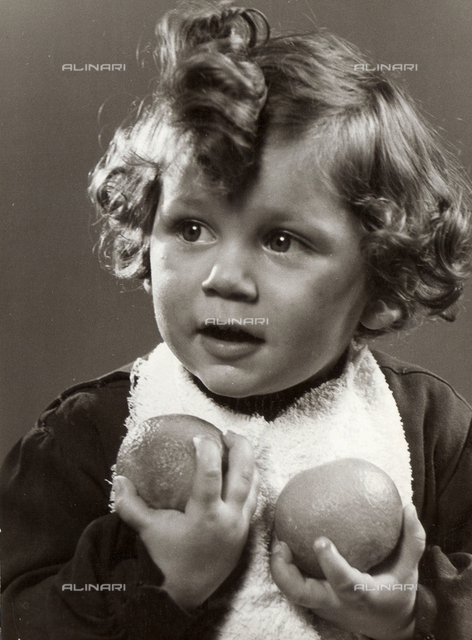 Photo of a little girl holding two oranges in her hands