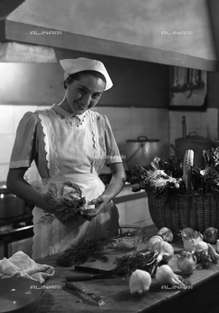 Young woman in the kitchen with cap and apron at a table with vegetables