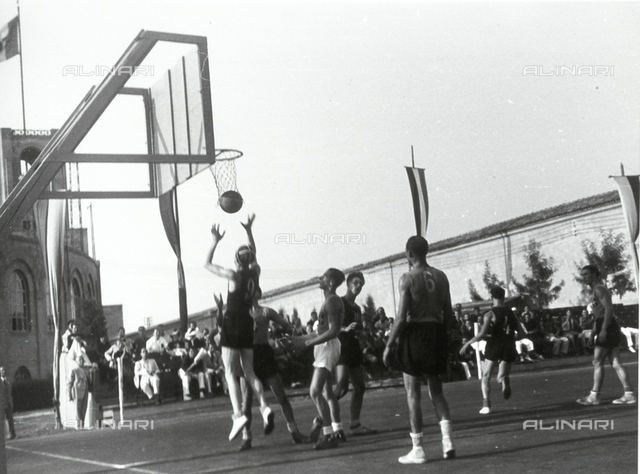 Spectators watch a basketball player take a shot during a game.