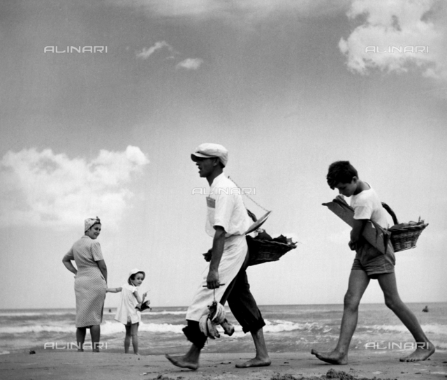 Two travelling salesmen walking on a beach. In the background there is a woman and a baby.
