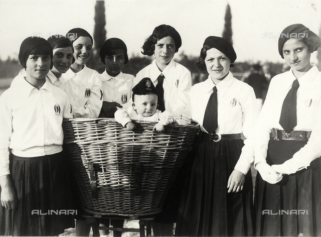 Group of girls in uniform during the Fascist period standing around a large wicker basket from which a baby wearing a cap is emerging.