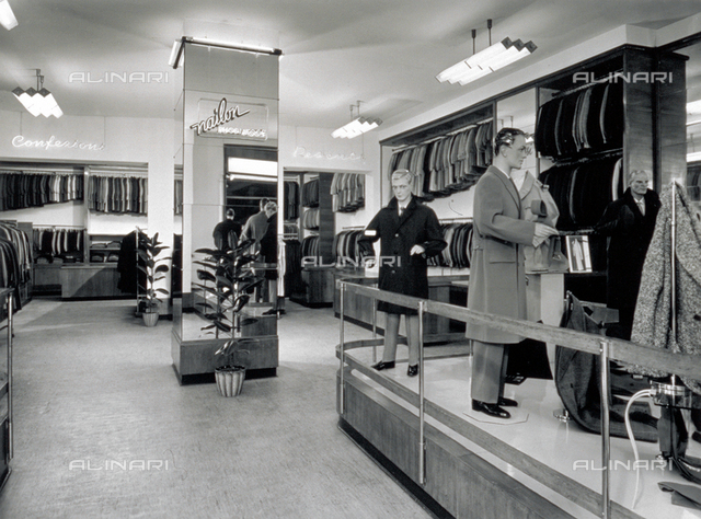 Interior of a men's clothing shop. In the foreground, to the right, a few manikins with winter coats