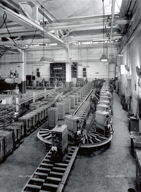 Interior of a factory of the Ideal Standard plant. A few workers are checking large radiators on the assembly chain