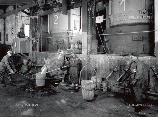 Interior of a factory of the Ideal Standard plant. A few workers in protective gear are working with molten metal