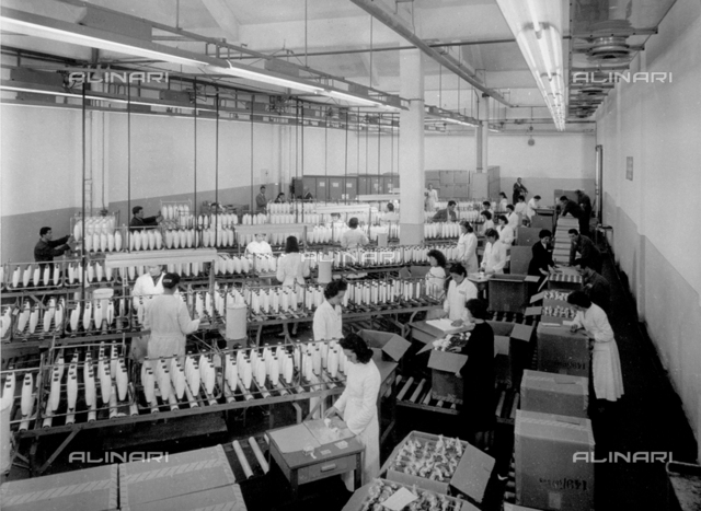 Interior of a textile factory. Numerous workers in white smocks are packing large reels of thread