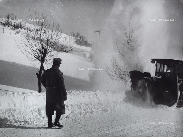 A man with his back to the camera on a snow-covered street watching a snow plow in operation.