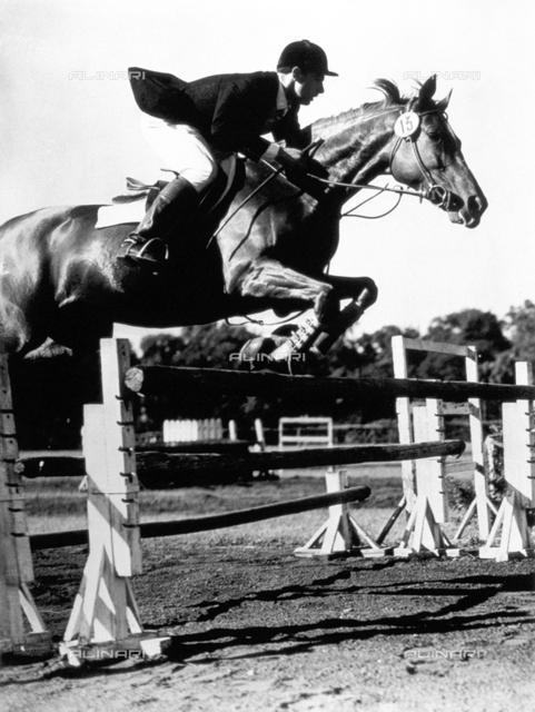 A jockey during a jump over a hurdle