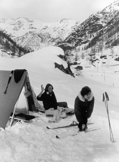 Portrait of two women next to a tent in a mountain landscape, covered with snow. One of the two women is shown putting her skis on, the other is sitting on a small bed