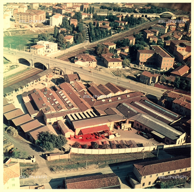 Aerial view of an industrial plant, next to a railroad and a street, near a neighborhood.