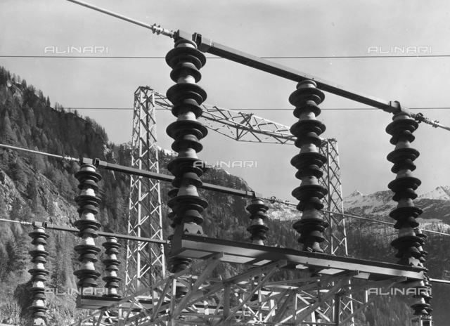 Electrical insulators on high tension railings. In the background, a mountain landscape is visible.