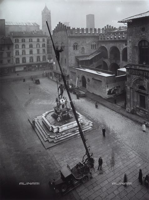 Placement of lamps for the illumination of Piazza del Nettuno in Bologna. In the center of the image, at bottom, an automobile is outfitted with a ladder on which an electrician is visible.