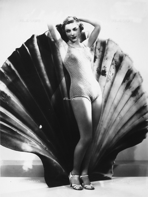 A model posing in front of a large shell wearing a one-piece bathing suit and sandals.