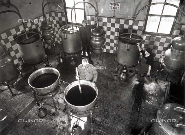 View from above of a room in a distillery, where three elderly workers are working around a few simple direct heat alembics