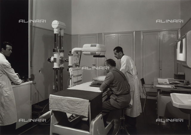 INAIL of Parma. Two doctors preparing a patient for a radiological exam on his arm.