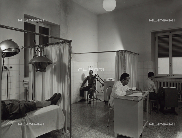 INAIL of Marghera. Two patients undergoing therapy. There is a doctor present, sitting at a desk.