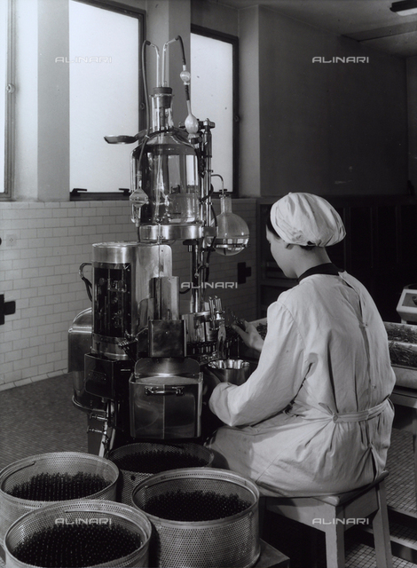A worker operating a machine that fills vials with medicine in the Recordati chemical/pharmaceutical factory.
