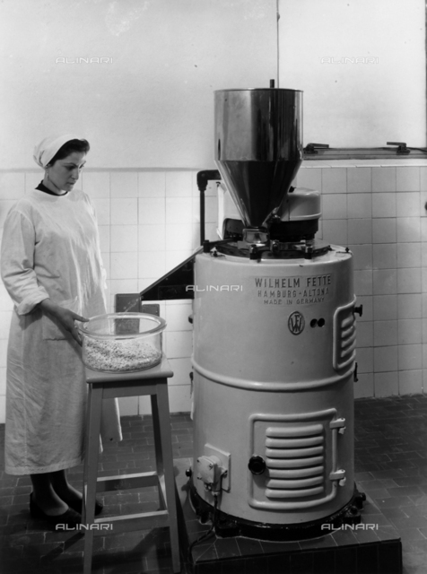 A worker operating a machine used for the production of medicinal tablets in the Recordati pharmaceutical factory.
