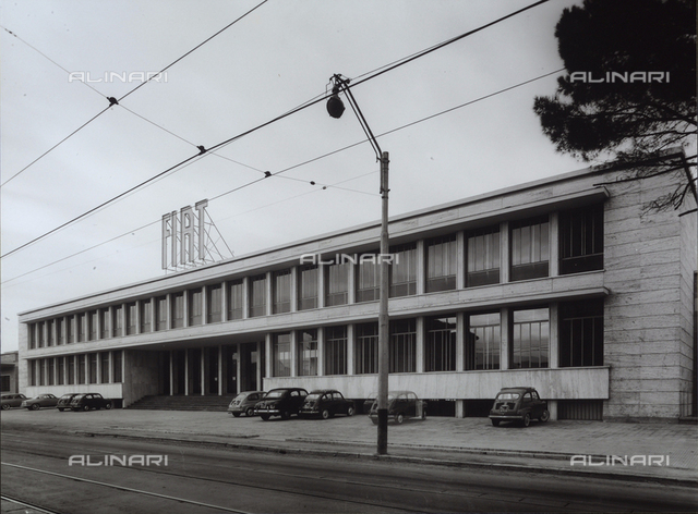Front of a FIAT factory. In the space opposite, there is a parking lot with some automobiles.
