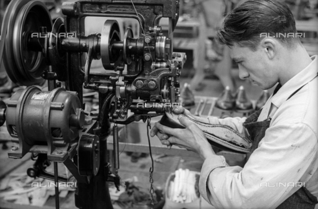 Closeup of a young worker to sew a shoe with the help of a machine inside the shoe factory Montanari