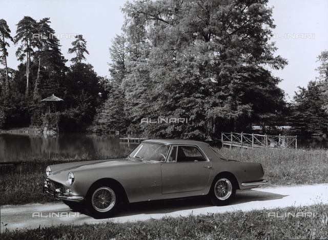 A Ferrari-Pininfarina parked in front of a pond surrounded by vegetation.