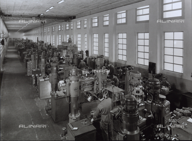 Inside of a FIAT factory with machinery and workers.