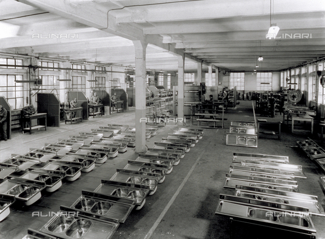Interior of a Broggi-Izar factory. On the floor several sinks. On either side of the room people are working
