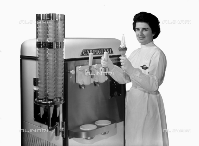 A woman in white smock shows the ice cream produced by a Carpigiani machine behind her